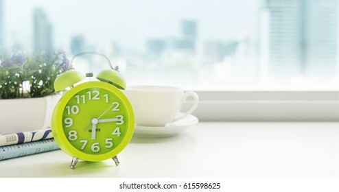 Morning concept. The table clock has a nice day with a cup of coffee and a newspaper flower pot, located near the window in a luxury apartment with city views in the morning.