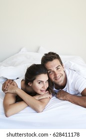 Morning couple relaxing in bed, smiling