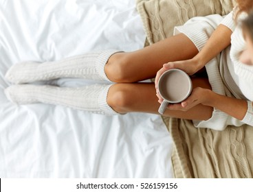 morning, coziness, winter and people concept - close up of young woman with cup of coffee or cacao in bed at home