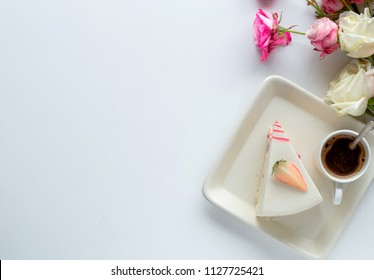 Morning cup of coffee, cake , and flower on white table from above. Beautiful breakfast. Flat lay style.