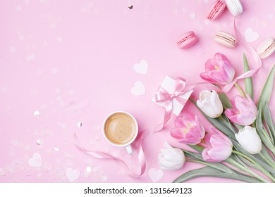 Morning cup of coffee, cake macaron, gift box and spring tulip flowers on pink background. Beautiful breakfast for Women day, Mother day. Flat lay.