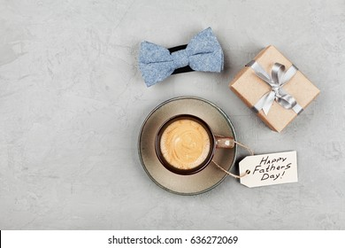Morning cup of coffee, gift and bowtie on stone table top view in flat lay style for breakfast on Happy Fathers Day