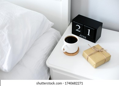 Morning cup of coffee, gift present, black wooden calendar on bedside table on Happy Fathers Day. Holiday concept