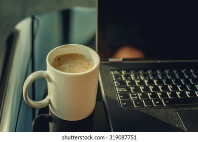 Morning cup of coffee and working space with laptop.