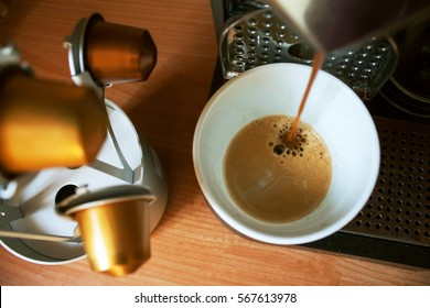 Morning cup of fragrant coffee from coffee machine on the wooden background with capsules holder