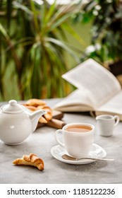 morning Cup of tea at Breakfast, kettle, book, light background.