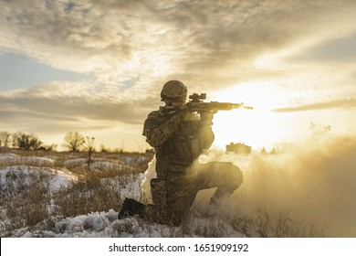 morning at dawn after a hard battle in the winter field or desert. exhausted army soldier Man. commandos with full equipment. Army man silhouette opposite the sun. battlefield sun backlight and smoke.