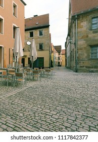 morning dawn, chairs and tables with umbrellas  for rest between old building lined of limestone on old street  in center Bayreuth, Franconia, Bavaria, Germany, Europe, wallpaper vertical  townscape