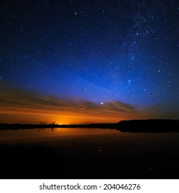 Morning dawn on a starry background sky reflected in the water of the lake.