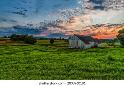 Morning dawn over a farm in a field. Valley farm at dawn. Sunrise over farm field. Early morning farm field at dawn