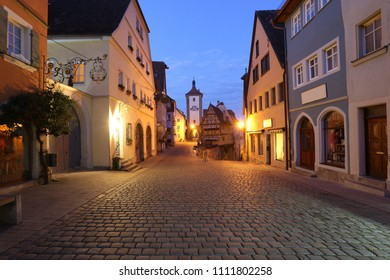 morning dawn view on center of historical medieval town of Germany - Rothenburg ob der Tauber, night scene of old street with coblestone on background dark blue sky, UNESCO, Franconia, Bavaria, Europe
