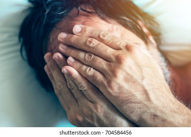 Morning depression and midlife crisis of a man in his 40s lying in bed in morning with symptoms like extreme sadness, frustration, anger and fatigue.