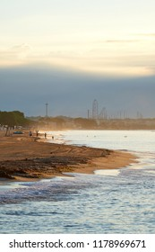 Morning energy / Mediterranean sea shore in the morning sun with waves and fun park in the background with cloudy sky