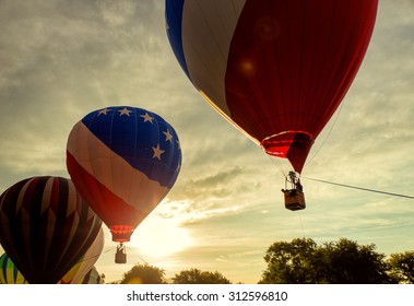 Morning / evening rise of hot air balloons with a cloudy open sky