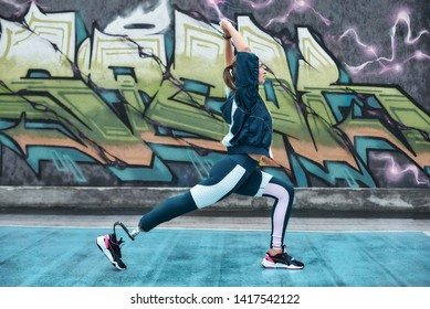 Morning exercises. Disabled young woman in sportswear with bionic leg doing stretching on stadium