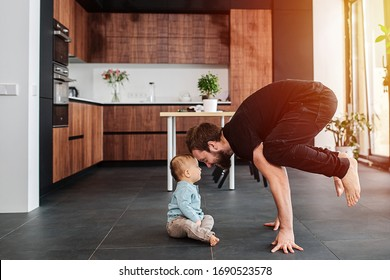 Morning family yoga exercises at home. Father standing on his fingers next to his infant baby. Family quarantine, domestic life in self-isolation. Sunset light from the windows.