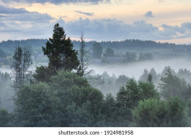 Morning fog in the countryside. Beautiful view of a small village in the forest. Picturesque summer rural landscape. Amazing nature of Russia. Old wooden houses in the distance. Vologda region, Russia