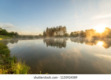 Morning fog on the forest lake, sunrise shot.