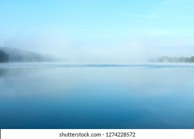 Morning fog on the lake on a summer day