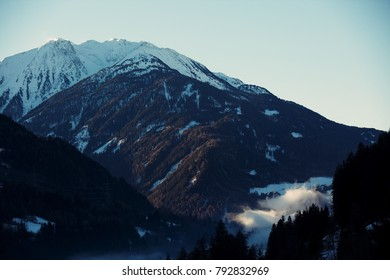 Morning fog rising in the Pitztal valley forming mystic scenery over the valley