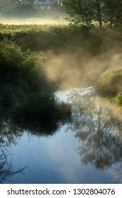 Morning fog in the village by the river in the sunlight
