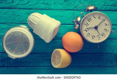 Morning fresh juice from lemon and orange. Handmade juicer, alarm clock, citrus fruit on a blue wooden background. Top view.