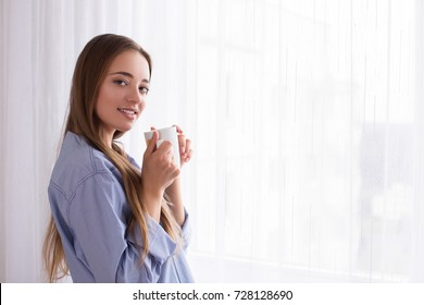 morning girl lies drinking coffee drink tea at the window of the house smile tenderness hair grooming