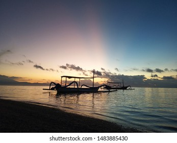 Morning glow. Beautiful sunrise sky. Fishing boat floating on sea at early morning. Tranquility nature landscape scene. Sanur Beach, Bali, Indonesia.