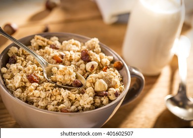 Morning granola breakfast with raisins, cranberries and hazelnuts served with almond milk on a wooden table