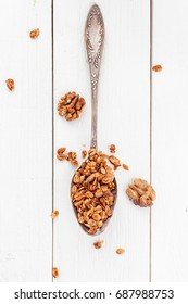 Morning granola breakfast with raisins and hazelnut on white wood  background