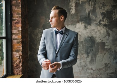 Morning of the groom. Groom morning preparation. Young and handsome groom getting dressed in a wedding shirt