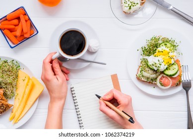 Morning habits of successful people. Day planning and healthy eating. Woman drink coffee and writing in notebook on the served for breakfast white wooden table. Top view, Selective focus