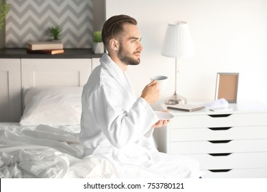 Morning of handsome young man drinking coffee while sitting on bed at home