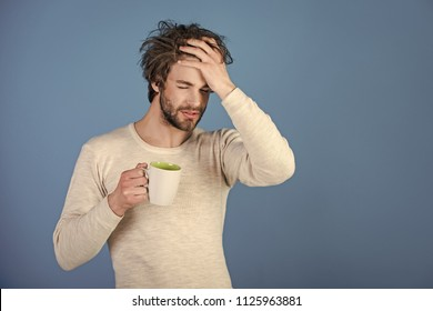 morning hangover. Sleepy guy with tea cup has headache on blue background. Man with disheveled hair drink mulled wine. Morning with coffee or milk. Cold and flu, single. Insomnia, refreshment and