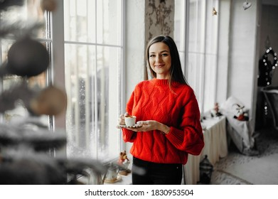 Morning of a happy woman in red sweater enjoying coffee in a winter holiday atmoshpere