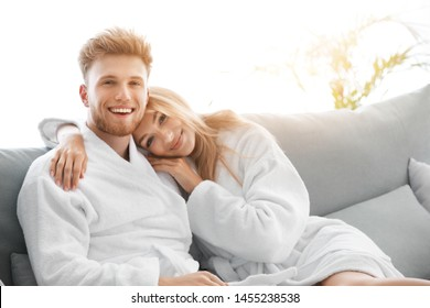 Morning of happy young couple in bathrobes at home