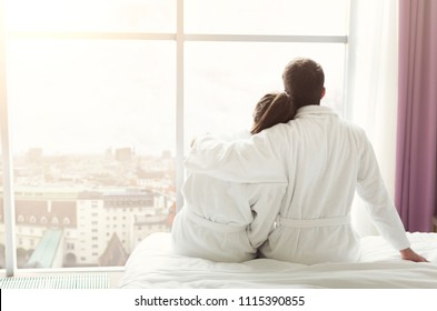 Morning of happy young couple looking out the window and resting in hotel room