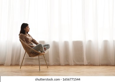 Morning harmony. Girl relaxing in wicker chair and daydreaming against window, side view, copy space