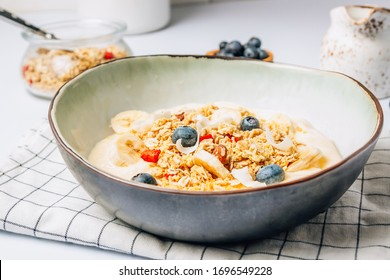 Morning healthy breakfast bowl with yogurt, muesli, blueberry, banana, coconut on the white background. Selective focus