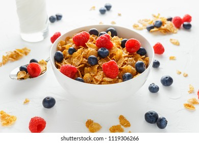Morning healthy Breakfast honey Cornflakes with fresh fruits of Raspberry, blueberries