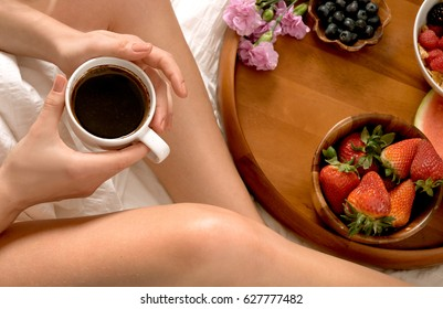 Morning and Healthy breakfast.  Woman eating breakfast and drinks coffee in the bed.