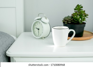 Morning home routine. White cup and alarm clock on bedside table