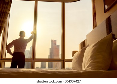 Morning in the hotel. Bed maid-up with white pillows in cozy room. Young businessman standing at window in confident pose looking at beautiful sunrise city scenery. Focus on cushion
