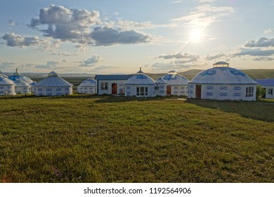 In the morning of hulunbuir, Inner Mongolia, the northeast of China, the sunshine on the grass and cylindrical mongolian yurts with white and bule pattern on its wall, and some clouds in the sky