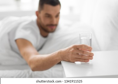 morning and hydration concept - close up of thirsty man reaching to glass of water on bedside table from bed at home