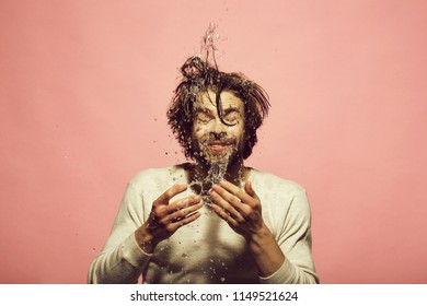 morning hygiene of man washing face with water drops. guy with long hair refreshing in underwear on pink background, skincare, health and wakeup, everyday life, barbershop