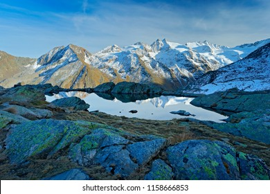 Morning in Italian Alps, mountains with smaůe lake in the rock, hills in the clouds, Alp, Gran Paradiso, Italy. Mountain landscpe with blue sky with white clouds.
