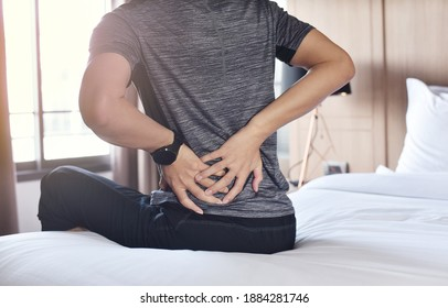 Morning joint stiffness and musculoskeletal syndromes, close up of young man has pain at the lower back