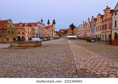 Morning landscape of main square in Telc. Fountain with statue of st. Margaret, towers of Holy Name of Jesus Church, Telc Castle and colorful medieval houses. A UNESCO world heritage site.