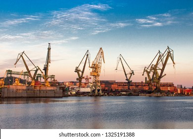 Morning landscape - view of the shipyard with historical cranes in the industrial part of the city Gdansk (Gdańsk) in Poland (Polska). The shipyard is close to the old town. Peaceful Motlawa river.